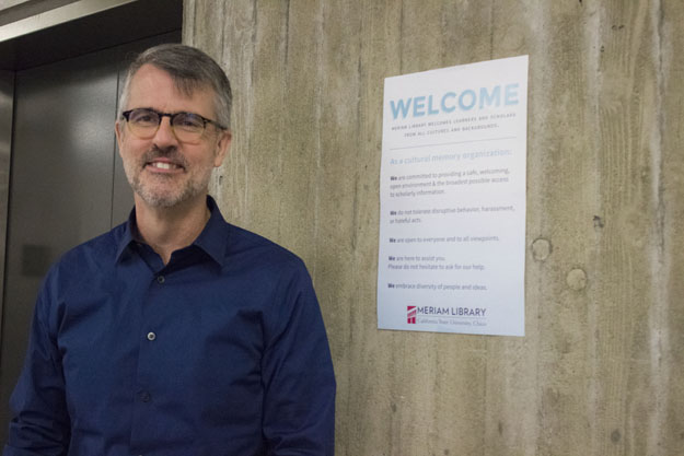 Photo of the Dean of Meriam Library standing next to a welcome poster