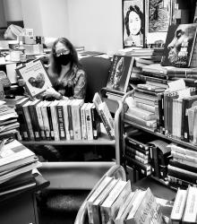Paula Holding Books, surrounded by books